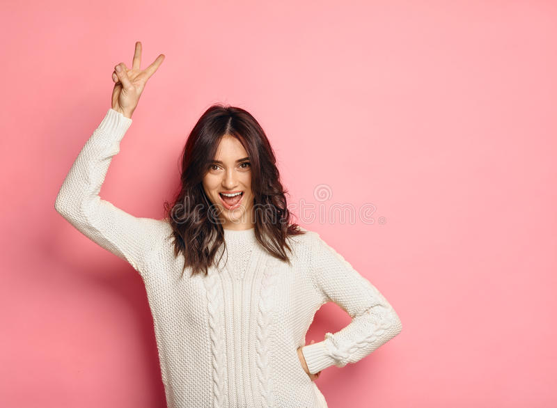 Positive girl showing peace sign on pink background. Portrait of positive girl showing peace sign wearing white cozy sweater on pink studio background royalty free stock images