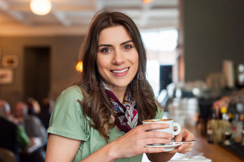 Positive girl taking a break sitting at bar in the cafe shop stock image