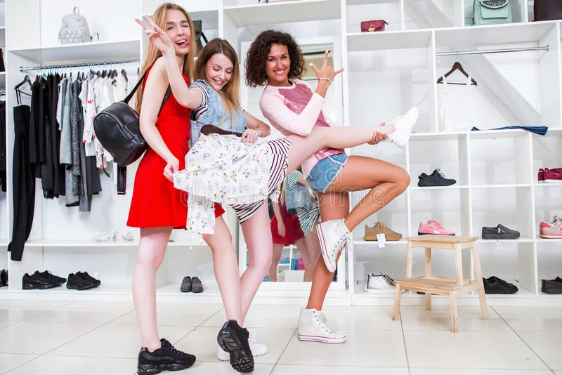 Positive girlfriends hanging out together in a stylish fashion shop fooling around showing rock-n-roll signs holding one. Friend s leg royalty free stock images