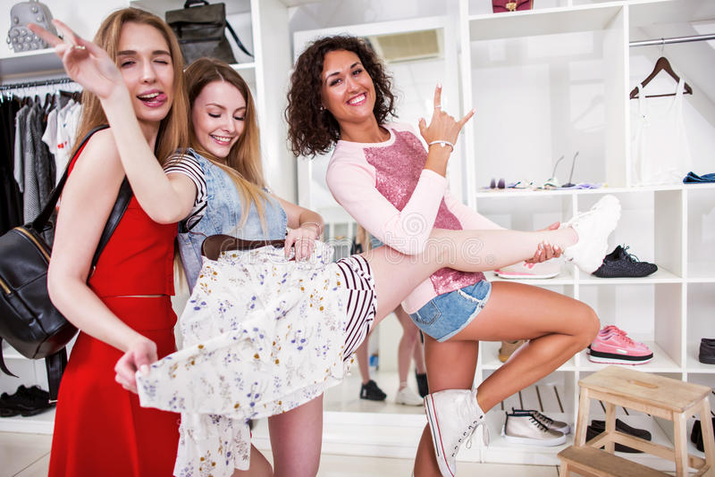 Positive girlfriends hanging out together in a stylish fashion shop fooling around showing rock-n-roll signs holding one. Friend s leg royalty free stock photo