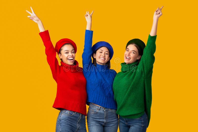 Positive Girls Gesturing V-Sign Smiling Posing Over Yellow Background royalty free stock photos