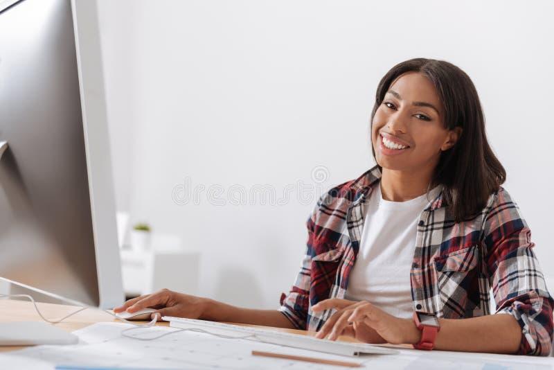 Positive glückliche Frau, die vor dem Computer sitzt stockbilder