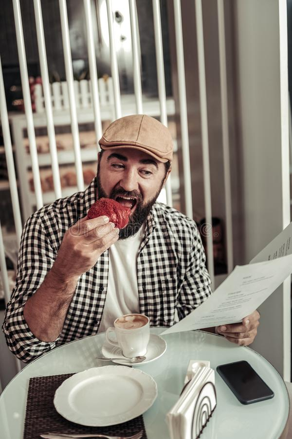Positive good looking man holding a menu. Dessert menu. Positive good looking man holding a menu while eating tasty pastry royalty free stock image