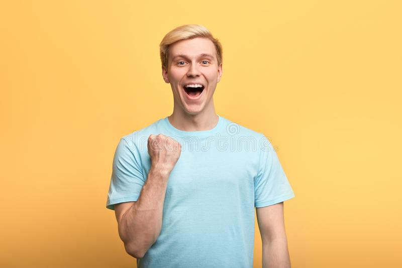 Positive gorgeous young emotional man raising clenched fists in hooray gesture stock images