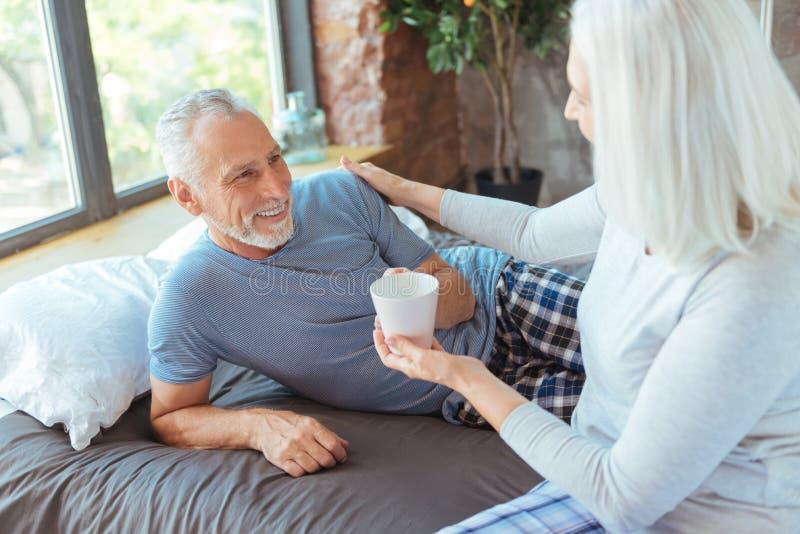 Positive Greisin, die ihrem liebevollen Ehemann Tasse Kaffee gibt lizenzfreies stockfoto