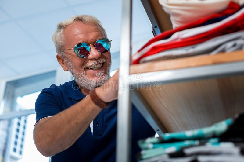 Positive grey haired man checking shopping shelf stock images