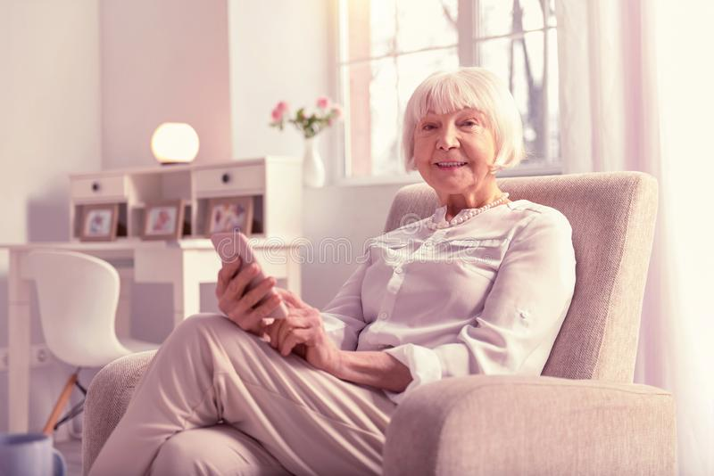Positive grey-haired mature lady checking her phone royalty free stock image