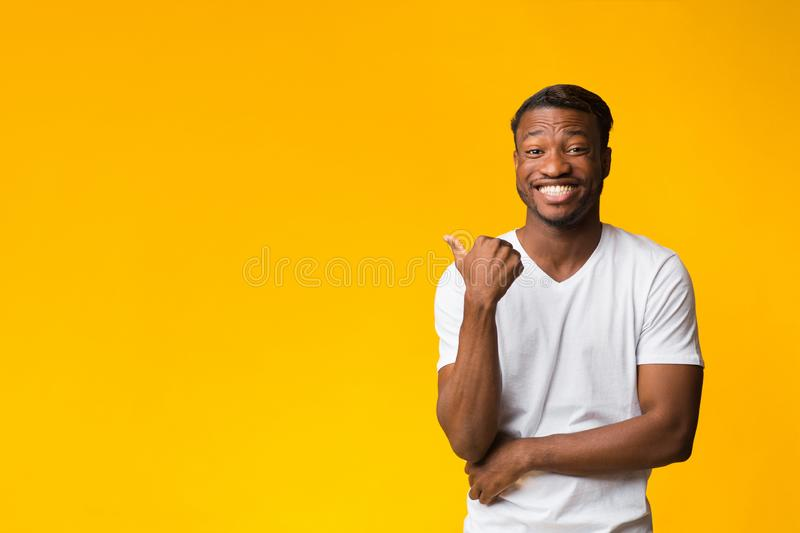 Positive Guy Pointing Thumb At Copy Space Standing In Studio stock photography