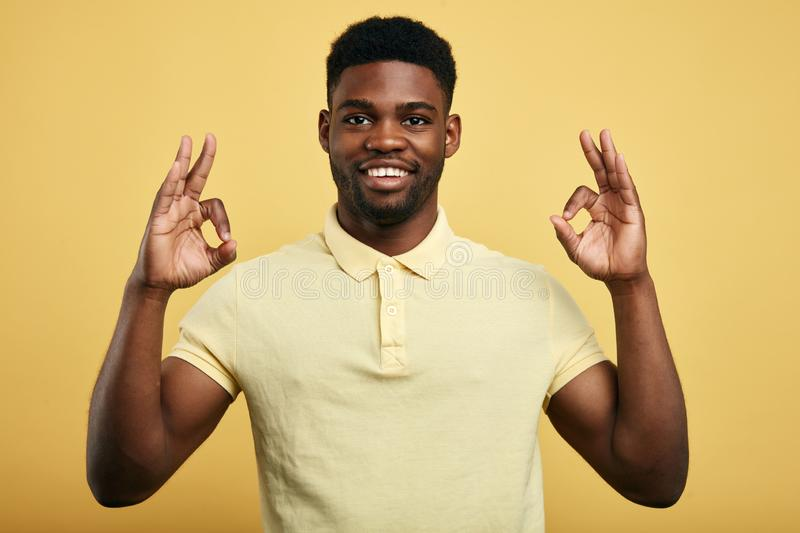 Positive guy shows OK gesture on a yellow background. royalty free stock photo