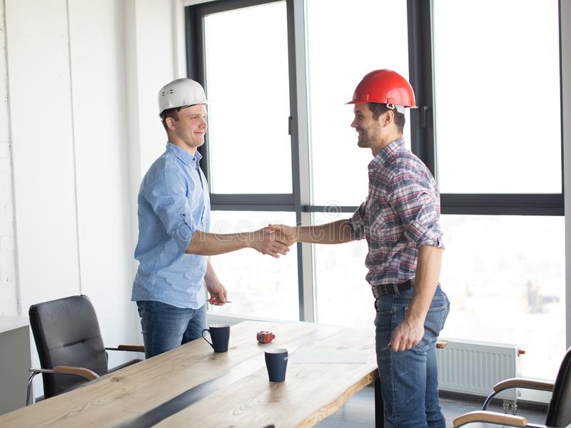 Positive guys shaking hands after successful deal royalty free stock images