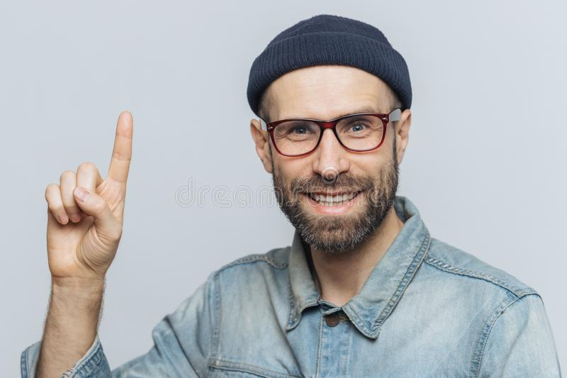 Positive handsome bearded male raises fore fimger, looks with cheerful expression directly intto camera, wears fashionable hat, sh stock image