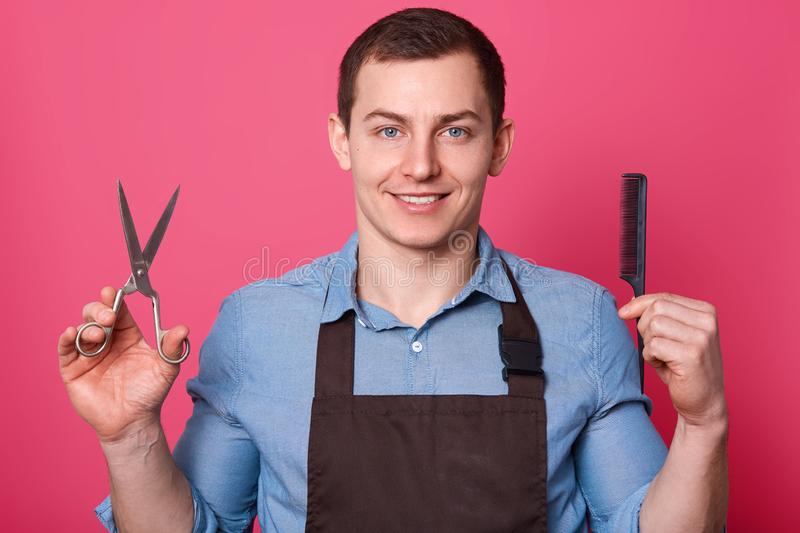 Positive handsome brunett barber shows scissors and comb, dressed in blue shirt and brown apron, ready to do hairstyle for men, stock photo