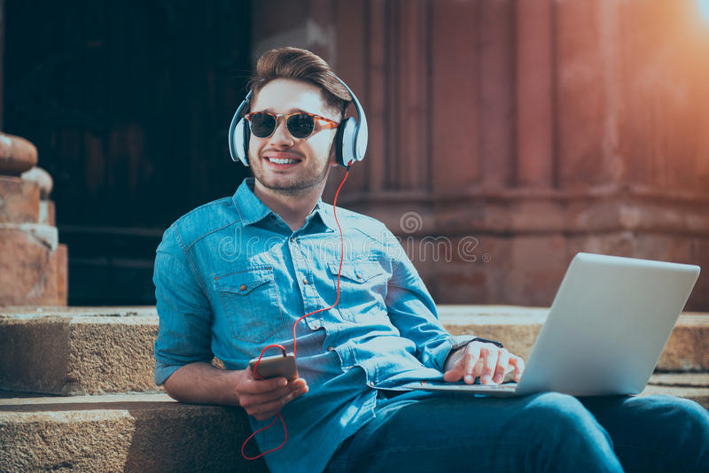 Positive handsome guy listening to music royalty free stock images