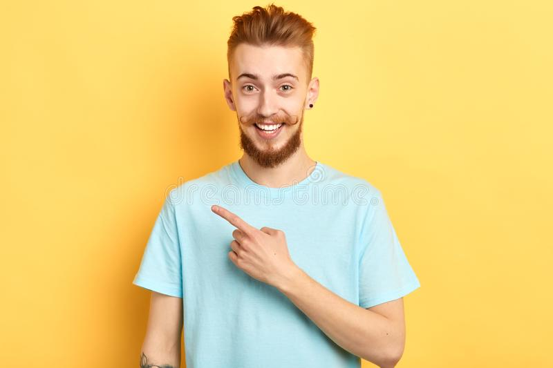 Positive handsome man poiting finger to copy space  on yellow background royalty free stock images