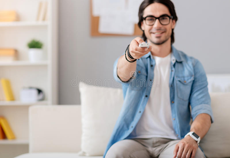 Positive handsome man watching TV stock images