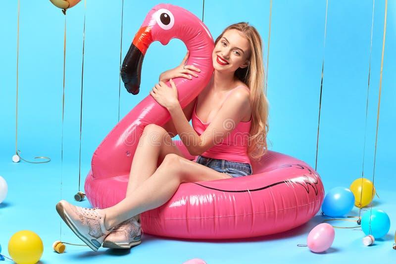 Positive happy blonde girl hugging flamingo mattress stock photography