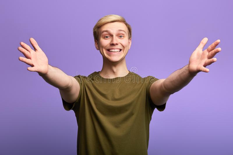 Positive happy handsome man welcoming people with his arms opened royalty free stock images