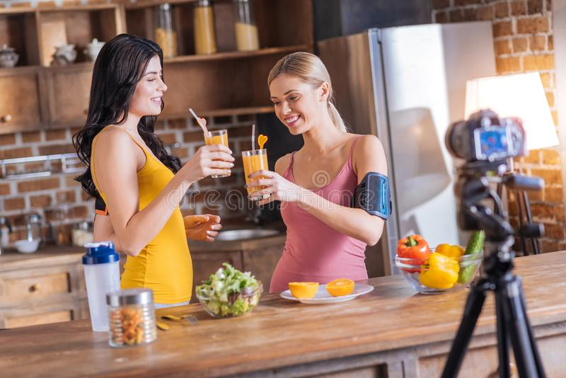 Positive happy women drinking fresh juice royalty free stock images