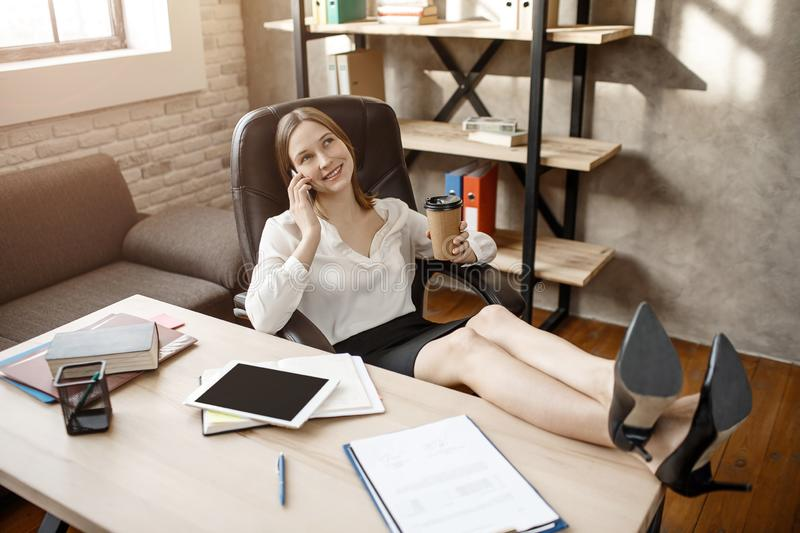 Positive happy young buisnesswoman sit at table and talk on phone. She hold legs on table. Model has break. She look up. stock photo