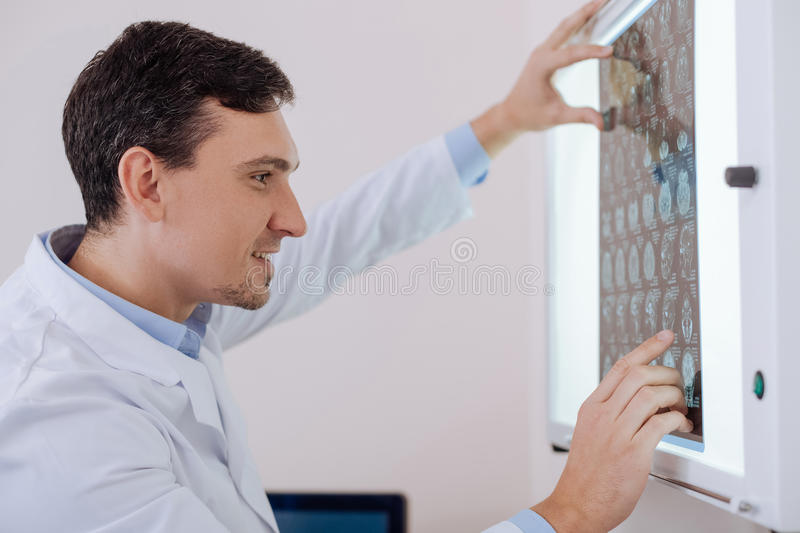 Positive hard working doctor working with CT brain scan. Professional radiologist. Positive hard working experienced man looking at the CT brain scan and smiling stock images