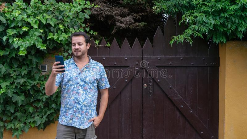 Positive Hipster reading news in social media and sharing the notification out. Person playing online with his cellphone, standing. And lean. Modern Guy typing royalty free stock image