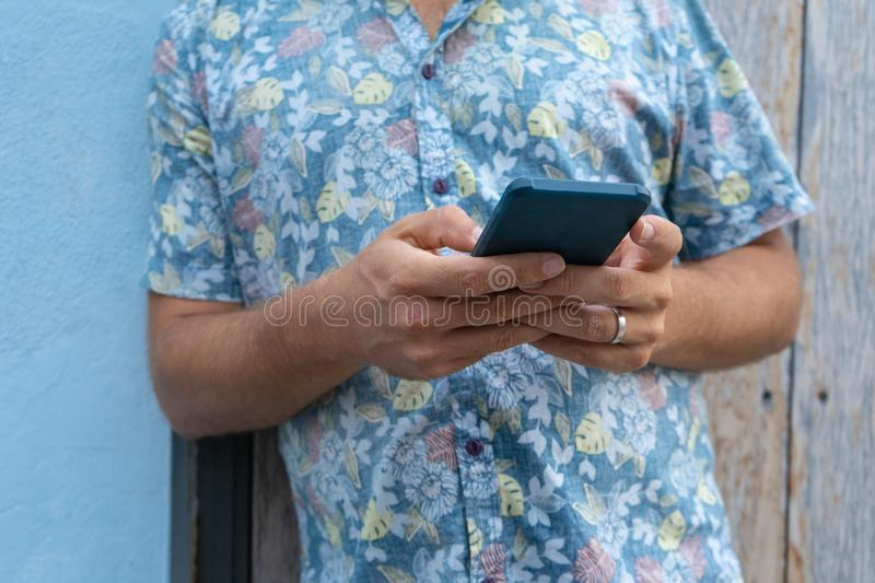 Positive Hipster reading news in social media and sharing the notification out. Person playing online with his cellphone, standing. And lean. Modern Guy typing stock photo