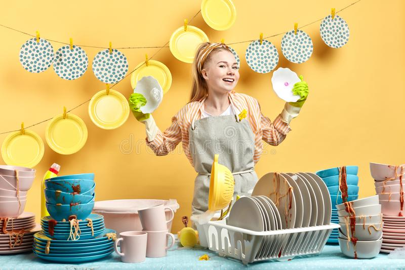 Positive housekeeper comparing differen dish soaps royalty free stock photo