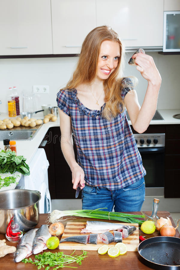 Positive housewife cooking saltwater fish. At domectic kitchen royalty free stock images