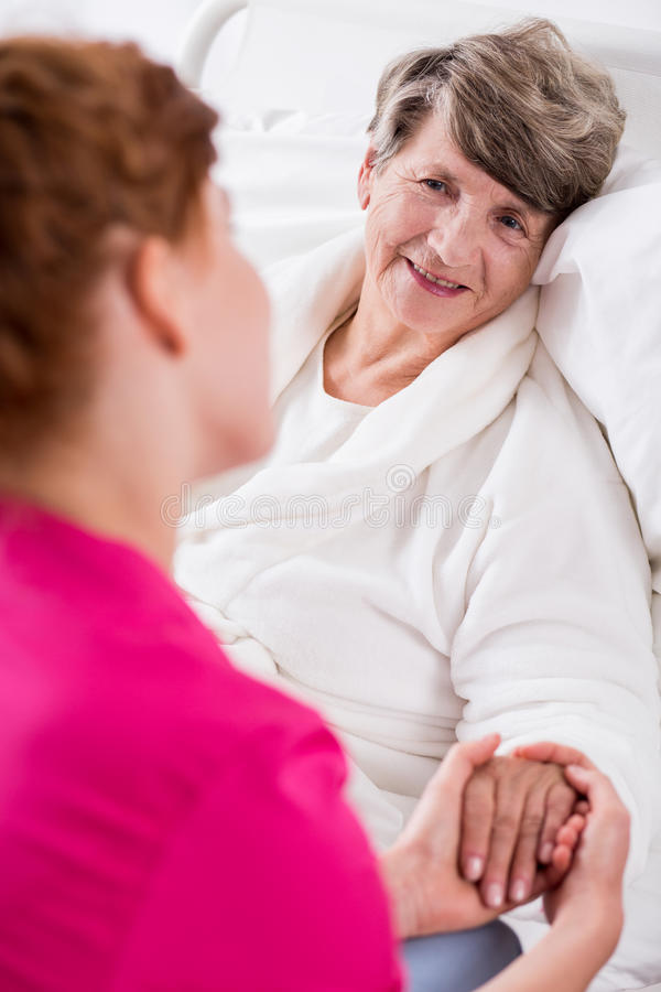 Positive impact on patient. Young nurse has positive impact on elderly patient royalty free stock photography