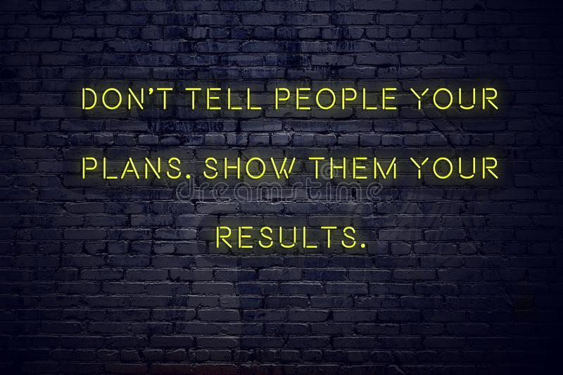 Positive inspiring quote on neon sign against brick wall dont tell people your plans show them your results royalty free illustration
