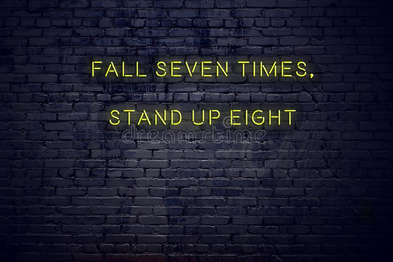 Positive inspiring quote on neon sign against brick wall fall seven times stand up eight stock illustration