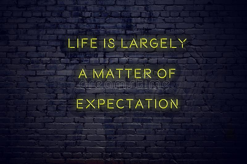 Positive inspiring quote on neon sign against brick wall life is largely a matter of expectation.  royalty free illustration
