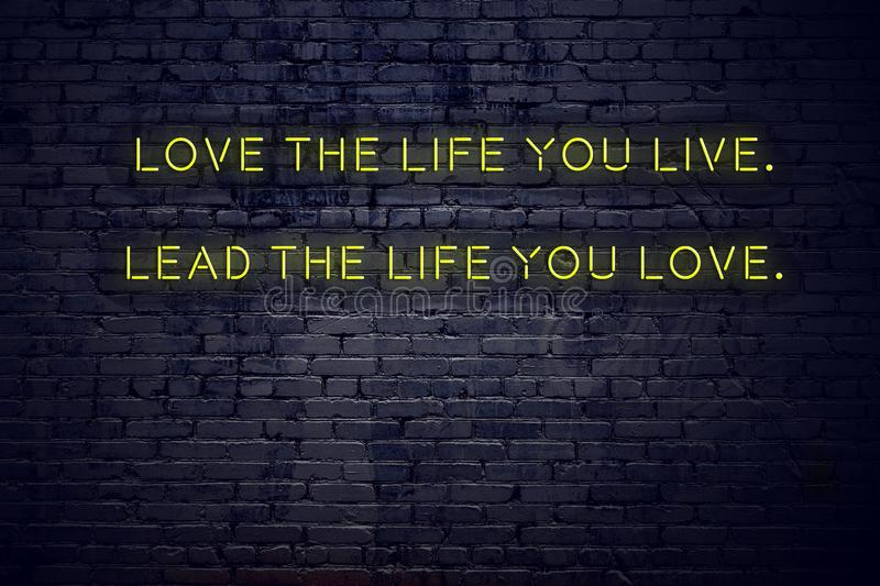 Positive inspiring quote on neon sign against brick wall love the life you live lead the life you love.  stock illustration