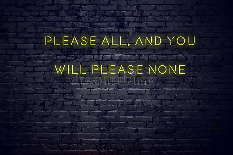 Positive inspiring quote on neon sign against brick wall please all and you will please none stock image