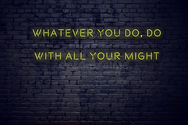 Positive inspiring quote on neon sign against brick wall whatever you do do with all your might.  stock image
