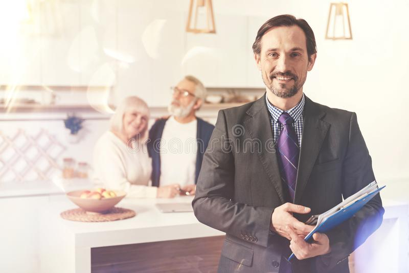 Positive insurance agent ready to work. Professional attitude. Positive handsome insurance agent holding folder and standing in the kitchen while visiting loving royalty free stock photography
