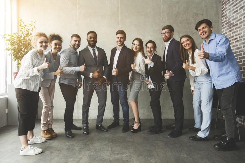 Positive interracial business people showing thumbs up royalty free stock photos