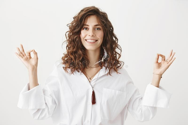 Positive joyful caucasian adult female with curly hair smiling and standing in meditating pose with zen gestures, being. Calm and confident over gray background stock photo