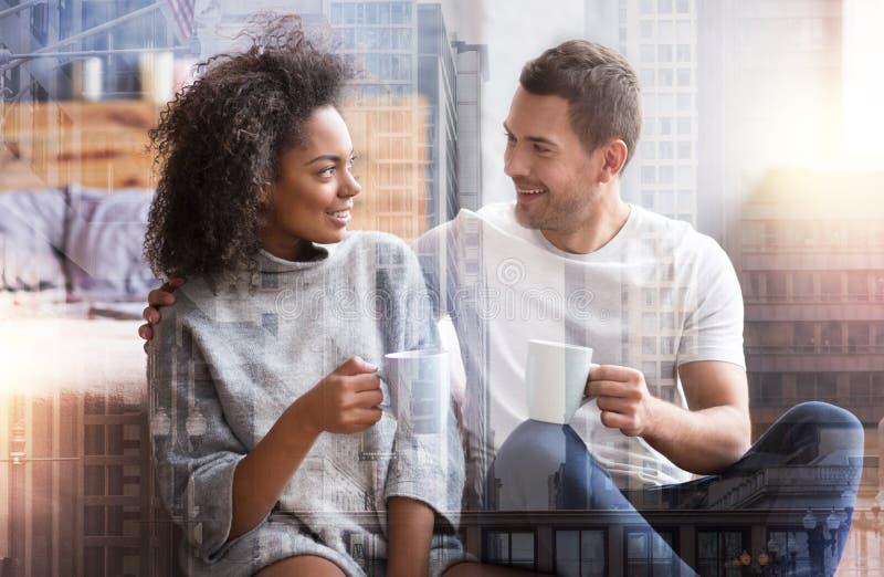 Positive joyful couple enjoying tea together stock images