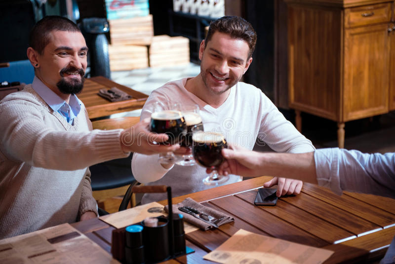 Positive joyful friends cheering with beer royalty free stock images