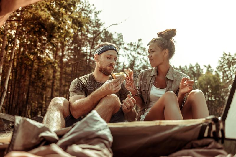 Positive joyful young couple eating sandwiches together royalty free stock photos