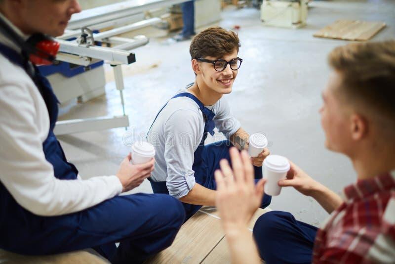 Positive junge Arbeitnehmer, die Bruch zusammen haben lizenzfreie stockbilder