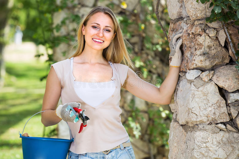 Positive junge Frau, die Gartenbauwerkzeuge im Garten hält stockbild