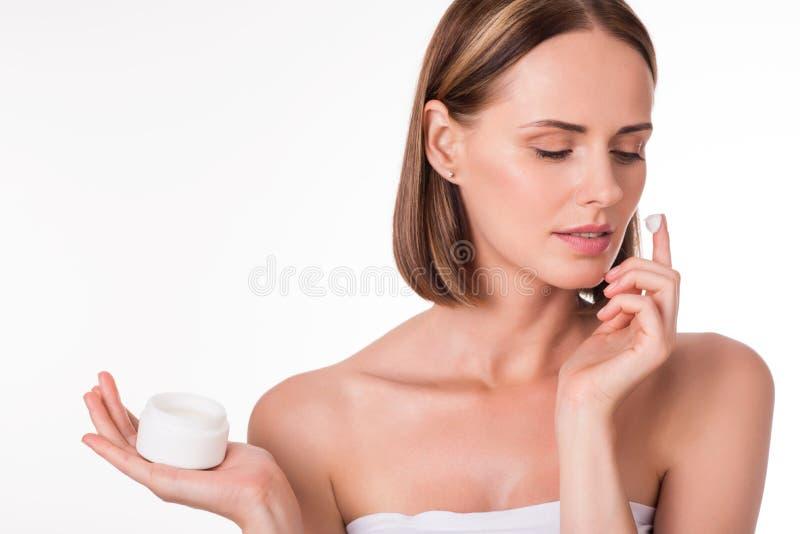 Positive junge Frau, die Kosmetik aufträgt lizenzfreie stockbilder
