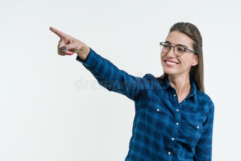 Positive junge Frau, die seinen Finger auf dem abstrakten hellen Hintergrund, einen digitalen Knopf auf einem abstrakten Schirm b lizenzfreie stockfotos