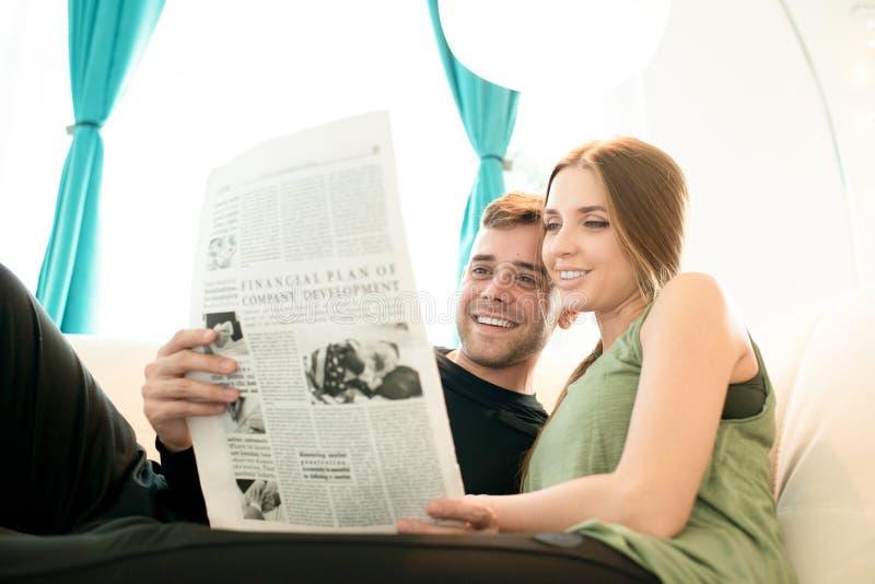 Positive junge Paarlesenachrichten zusammen stockbilder