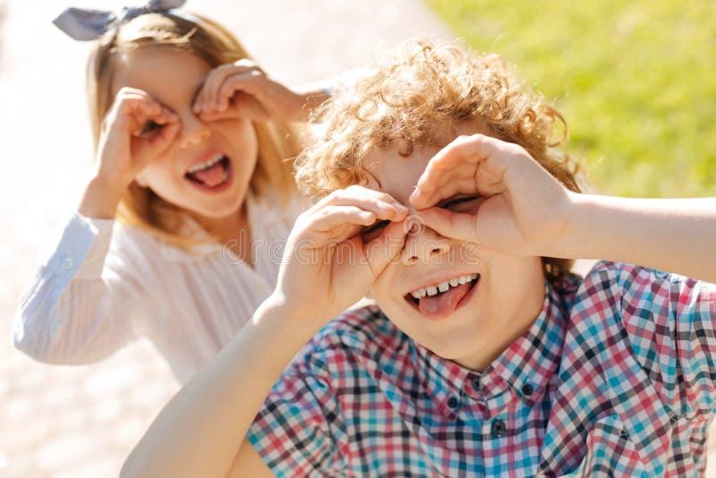 Positive Kinder, die auf Kamera mit Vergnügen aufwerfen stockbilder