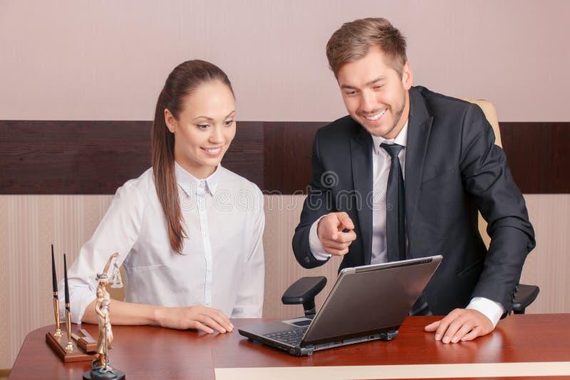 Positive Kollegen, die am Tisch sitzen lizenzfreie stockfotos