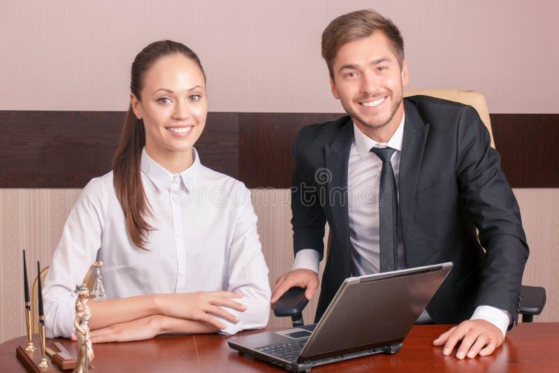Positive Kollegen, die am Tisch sitzen lizenzfreies stockbild