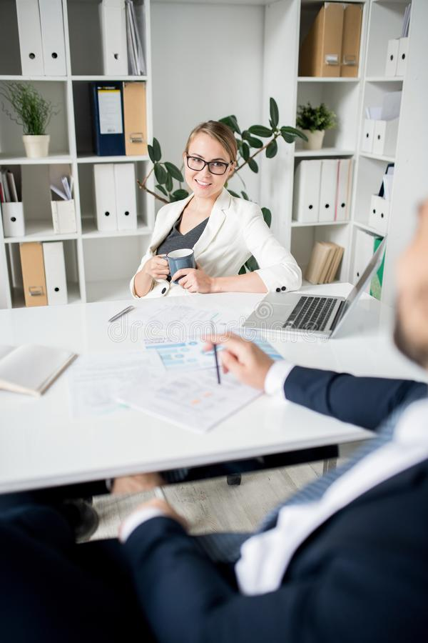 Positive lady boss listening to managers report stock image